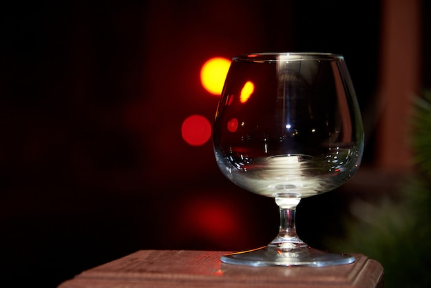 Bicchiere di vino vuoto su uno sfondo scuro sfocato con un bokeh.