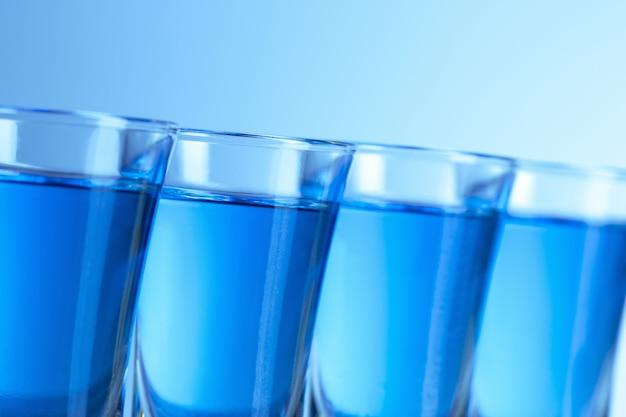 Bicchiere di vodka con ghiaccio sul blu