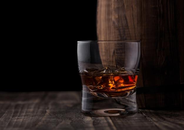 Bicchiere di whisky con cubetti di ghiaccio accanto alla botte di legno