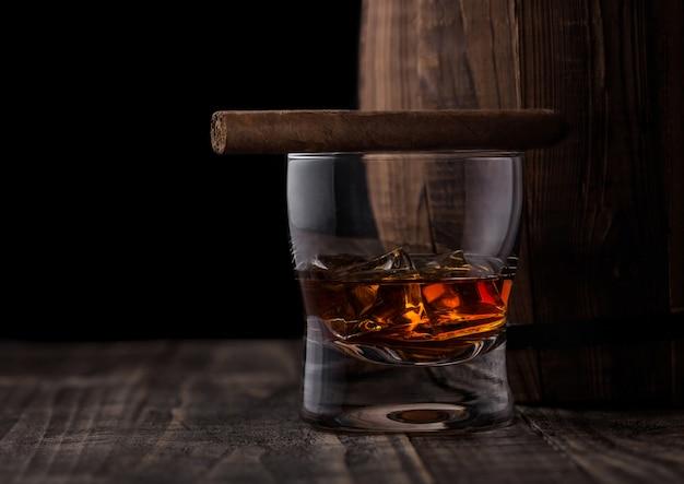 Bicchiere di whisky con cubetti di ghiaccio e sigaro accanto alla botte di legno