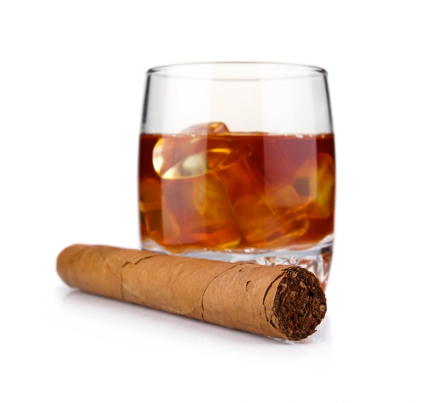 Bicchiere di whisky con cubetti di ghiaccio e sigaro di avana isolato