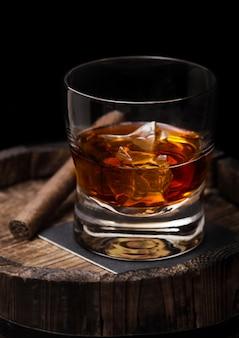Bicchiere di whisky con cubetti di ghiaccio e sigaro sopra la canna di legno