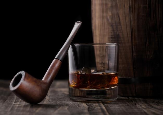 Bicchiere di whisky con cubetti di ghiaccio e tubo di fumo d'epoca accanto alla botte di legno