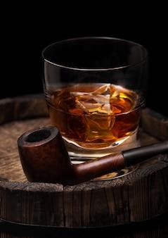 Bicchiere di whisky con cubetti di ghiaccio e tubo di fumo vintage in cima a botte di legno