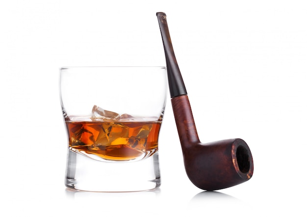 Bicchiere di whisky con cubetti di ghiaccio e tubo di fumo vintage