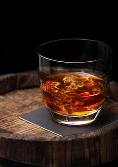 Bicchiere di whisky con cubetti di ghiaccio in cima a botte di legno