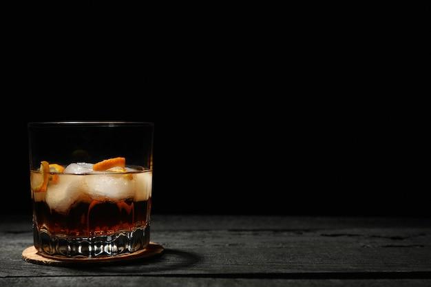 Bicchiere di whisky con cubetti di ghiaccio su fondo di legno scuro, spazio per il testo