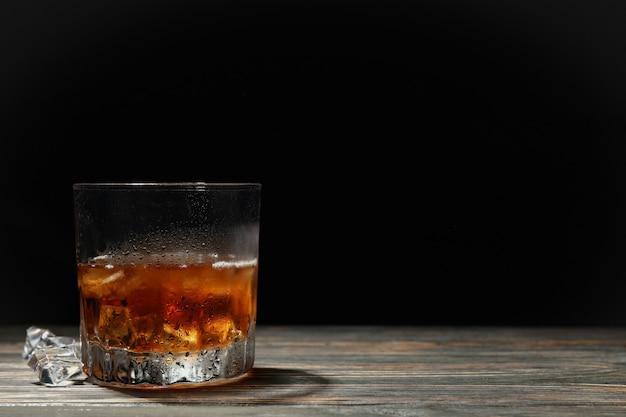 Bicchiere di whisky con cubetti di ghiaccio su fondo in legno, spazio per il testo