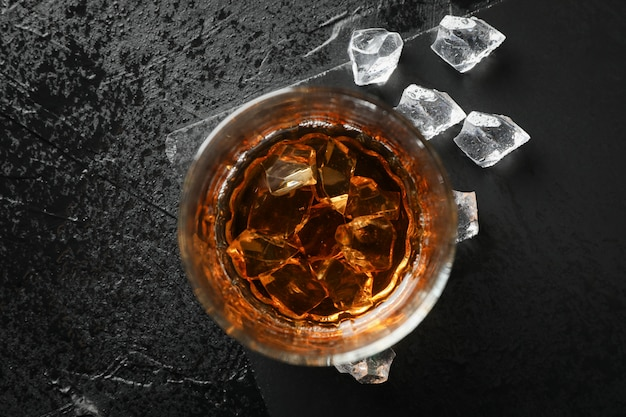 Bicchiere di whisky con cubetti di ghiaccio su sfondo nero, vista dall'alto
