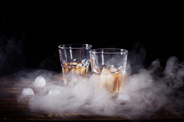 Bicchiere di whisky con fumo e ghiaccio su un tavolo di legno