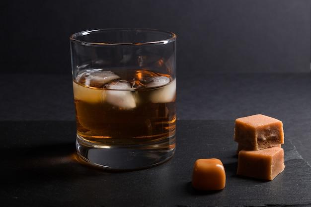 Bicchiere di whisky con ghiaccio e caramelle al caramello su una tavola di pietra nera ardesia. vista laterale