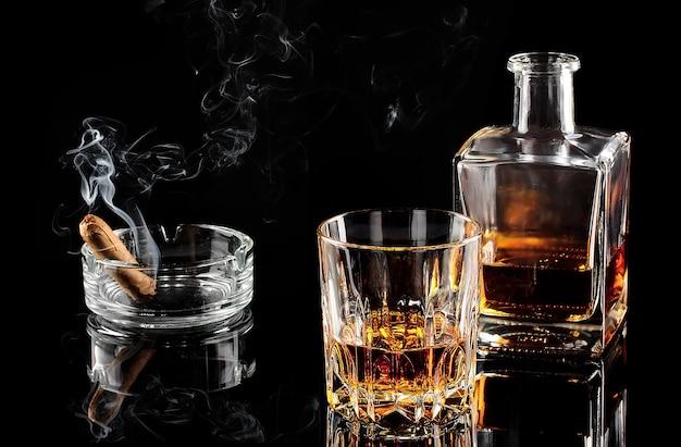 Bicchiere di whisky con ghiaccio e una caraffa di sigaro fumante