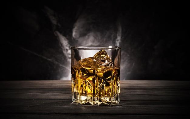 Bicchiere di whisky con ghiaccio su sfondo nero