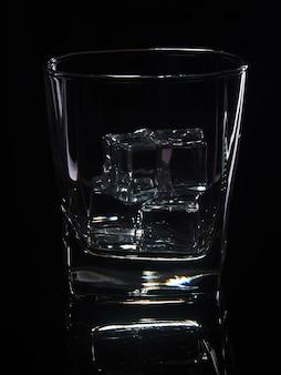 Bicchiere di whisky con ghiaccio su uno sfondo nero con la riflessione