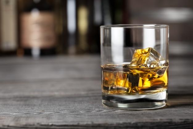 Bicchiere di whisky con ghiaccio sulla barra rack