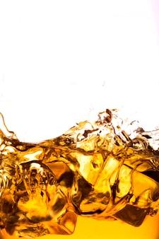 Bicchiere di whisky con splash, isolato su sfondo bianco