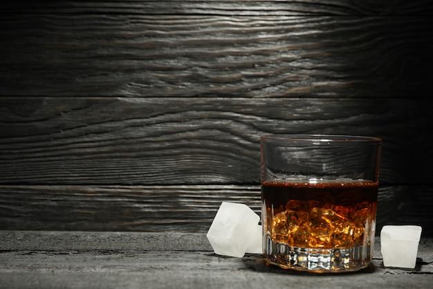 Bicchiere di whisky e cubetti di ghiaccio su fondo di legno scuro, spazio per il testo