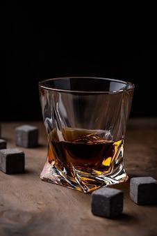 Bicchiere di whisky e pietre. stile dark mood