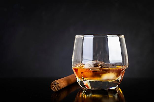Bicchiere di whisky e sigari su sfondo scuro.