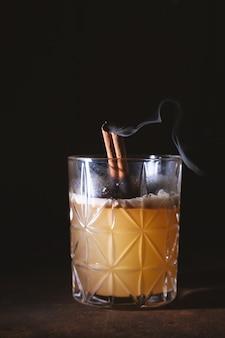 Bicchiere di whisky scozzese di arancia cocktail di alcol con fumo di bastoncini di cannella