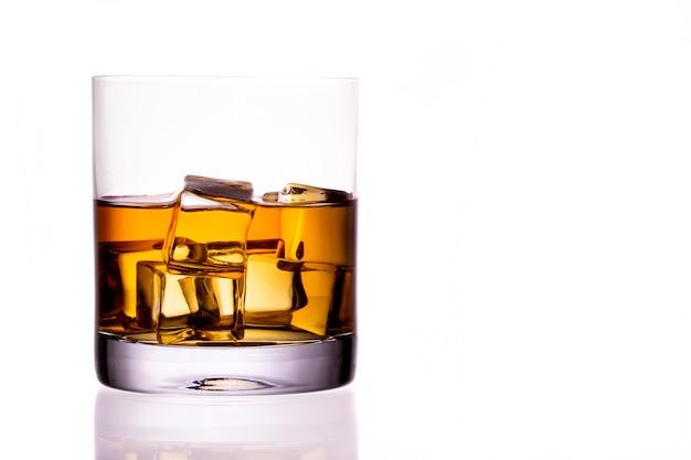 Bicchiere di whisky scozzese e ghiaccio su uno sfondo bianco