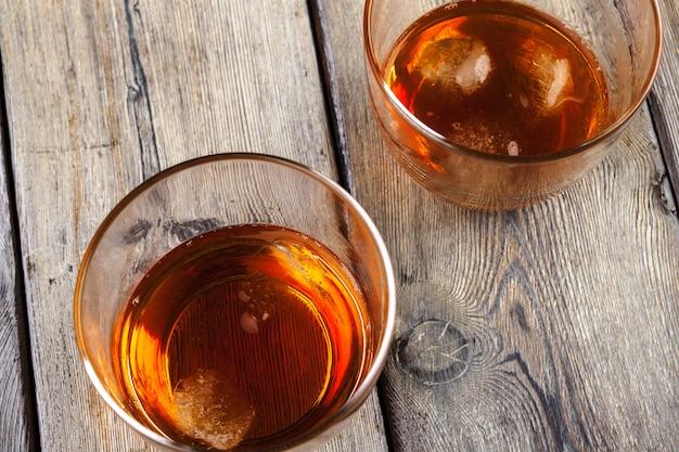 Bicchiere di whisky su ghiaccio con bottiglia sulla barra di legno