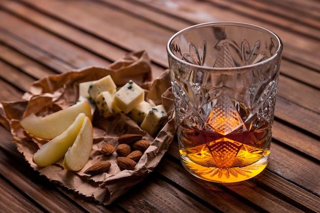 Bicchiere di whisky su un tavolo di legno con uno spuntino