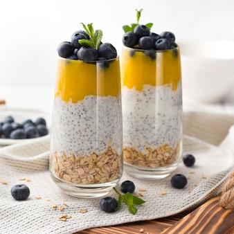 Bicchiere di yogurt con mirtilli e mousse di mango, semi di chia e farina d'avena su un vassoio di legno.