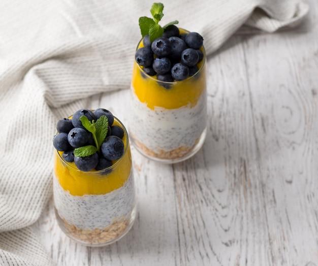 Bicchiere di yogurt con mirtilli e mousse di mango, semi di chia e farina d'avena.