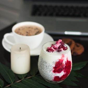 Bicchiere di yogurt con semi di chia e lamponi freschi sul foglio