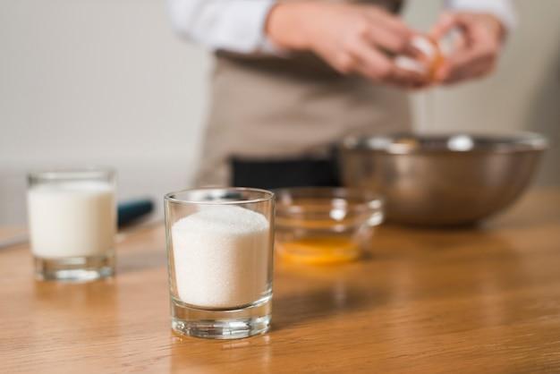 Bicchiere di zucchero in primo piano con sfocatura donna rompere l'uovo nella ciotola