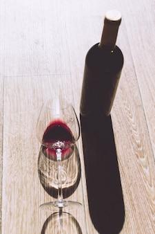 Bicchiere e bottiglia con vino rosso
