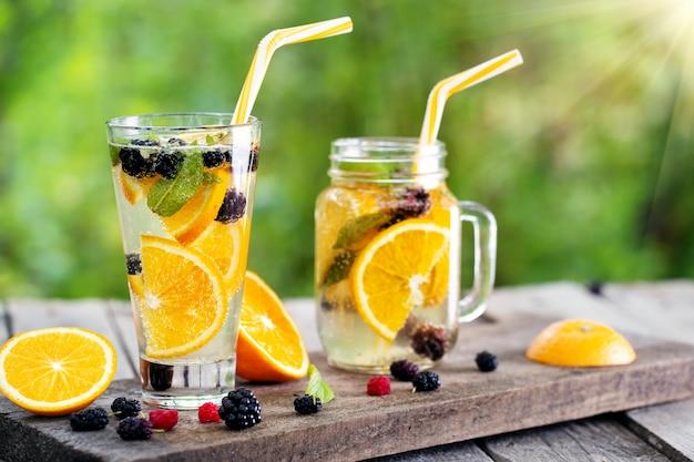 Bicchiere e una lattina con un cocktail d'arancia limonata e bacche
