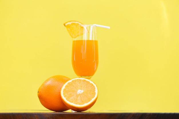 Bicchiere estivo di succo d'arancia con frutta arancione pezzo con sfondo giallo