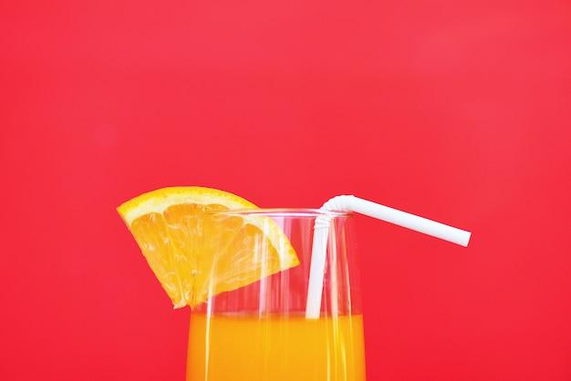 Bicchiere estivo di succo d'arancia con frutta arancione pezzo su rosso con copyspace