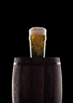 Bicchiere freddo di birra artigianale sul vecchio barilotto di legno su sfondo nero con rugiada e bolle