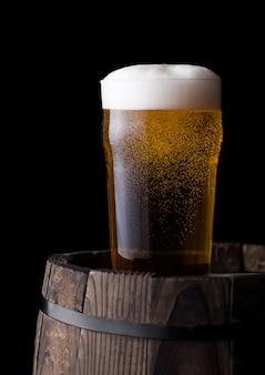 Bicchiere freddo di birra artigianale sul vecchio barilotto di legno su sfondo nero