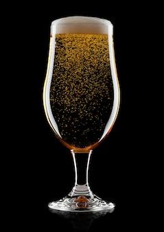 Bicchiere freddo di birra chiara birra artigianale con schiuma e bolle su sfondo nero