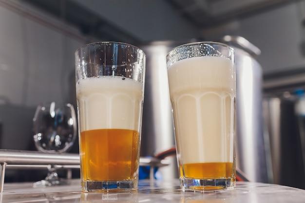 Bicchiere gelido di birra leggera sul bancone del bar.