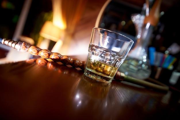 Bicchiere inclinato di whisky sulla barra con un narghilè su uno sfondo sfocato.