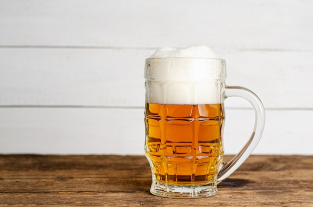 Bicchiere pieno di birra bionda su backgroud di legno bianco