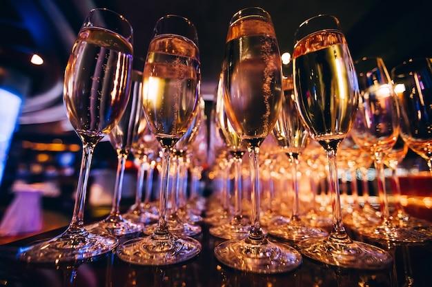 Bicchiere pieno di champagne in una discoteca. molti bicchieri di champagne al bar. bolle di champagne in un bicchiere.