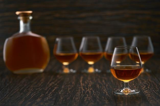 Bicchiere pieno di cognac sul tavolo, tre bicchieri di cognac e una bottiglia piena di cognac.
