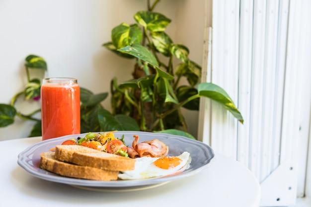 Bicchiere sano di frullati con pancetta; insalata; pancetta e uova fritte sul piatto di ceramica sul tavolo bianco