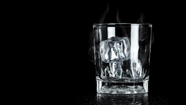 Bicchiere vuoto con cubetto di ghiaccio e copyspace. blocchi di ghiaccio per bevande.