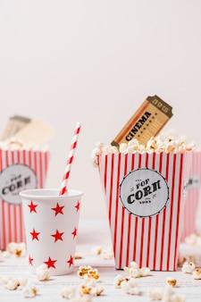Bicchieri a forma di stella con scatola di paglia e popcorn su sfondo bianco