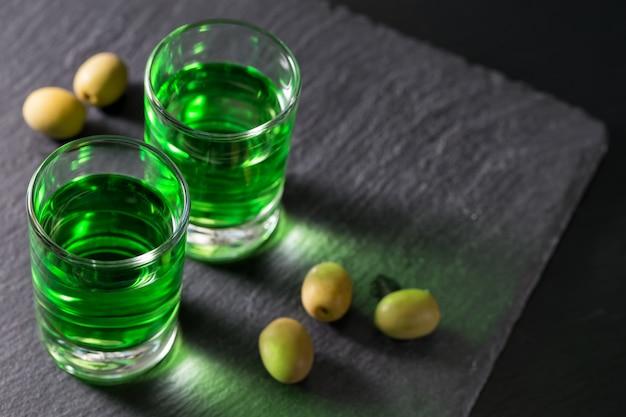 Bicchieri con assenzio e olive verdi