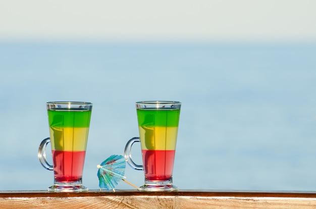 Bicchieri con cocktail colorati sullo sfondo del mare