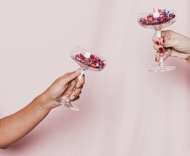 Bicchieri con coriandoli che tostano per i nuovi anni