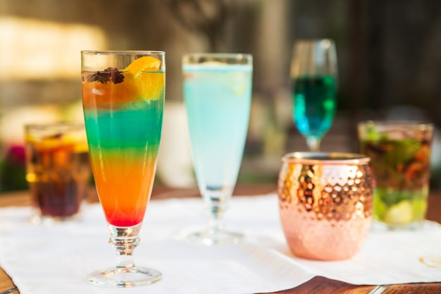 Bicchieri con freschi cocktail estivi o moctail di colore arancione e blu con frutta e ghiaccio